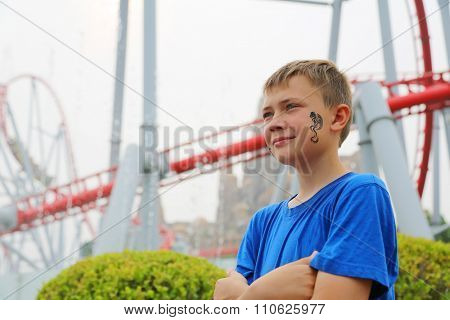 Boy on a background of a roller coaster at an amusement park. Drawing a dragon on her cheek.
