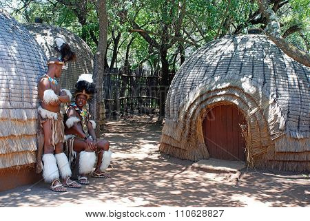 Zulu Men Wearing Warrior Dress Near Tribal Straw House, South Africa.