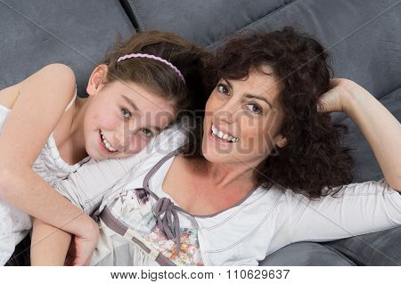 Happy Mother And Daughter Looking At Each Other While Relaxing On Sofa