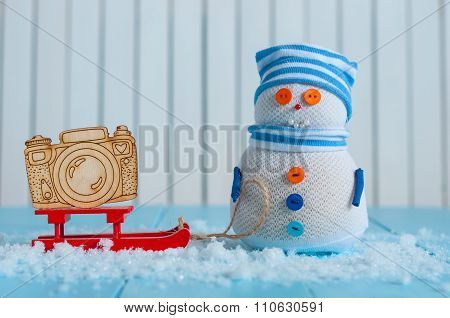 Handmade snowman in striped cap with red sled and toy camera on snow In winter. Christmas postcard b