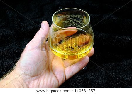 Hand Of A Man With A Glass Of Brandy On The Black Velvet