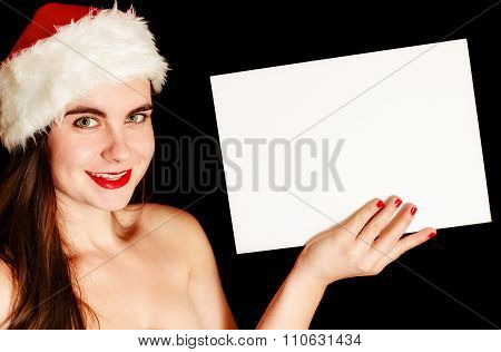 Girl Wearing Santa Hat And Holding Blank Sheet Of Paper