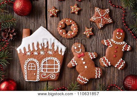 Gingerbread house, man and woman couple, stars christmas cookies with new year tree decorations fram