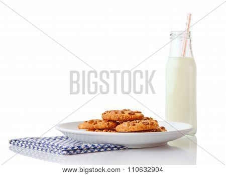 Pile of homemade peanut butter cookies on white ceramic plate on blue napkin and bottle of milk