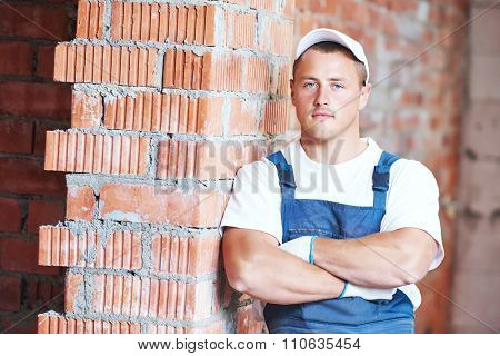 Construction worker. Mason bricklayer standing near brickwall at construction site