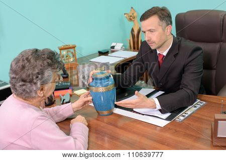 Funeral director with woman, looking at urn