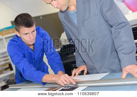 Young man cutting out a print