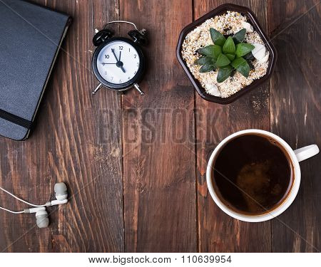 Coffee, Alarm Clock, Succulent Plant And Earphones On The Table