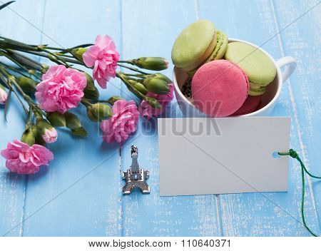 Blank Paper Card, Macarons, Flowers And Souvenir Eiffel Tower On The Table