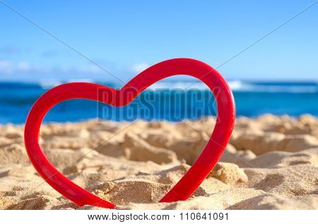 Red Heart On The Sandy Beach Background