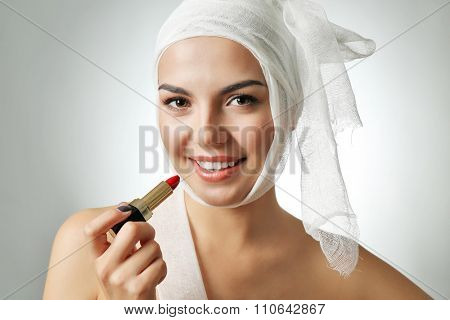 Young emotional woman with a gauze bandage on her head, holding lipstick, on grey background