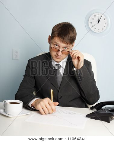 Serious Businessman Looking Above Glasses