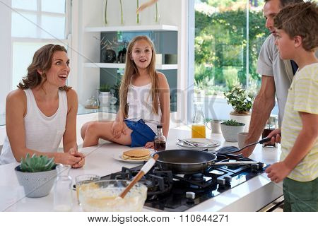 Happy caucasian family standing around stove, son making pancakes on stove