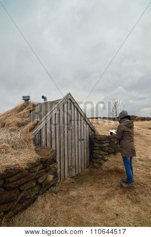 Tourist looking at traditional turf house in iceland