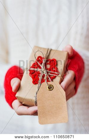 Woman In Knitted Sweater Holding A Present. Gift Is Packed In Craft Paper With Crocheted Snowflake.