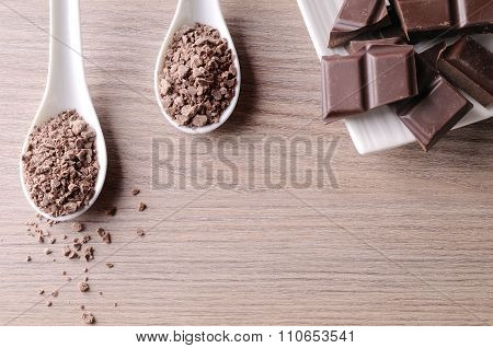 Portions And Chocolate Chips On White Container On Wood Top