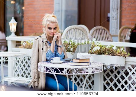 Young charming woman posing while sitting at the table with open portable net-book