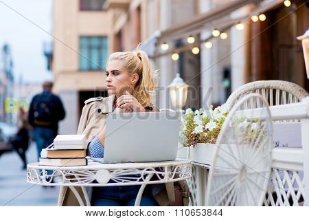 Young charming lady looking away while sitting in front open laptop computer in sidewalk cafe