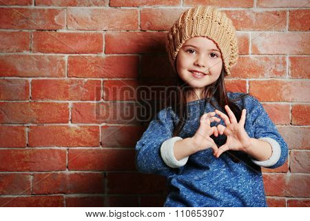 Portrait of little fashion kid girl on bricks wall background