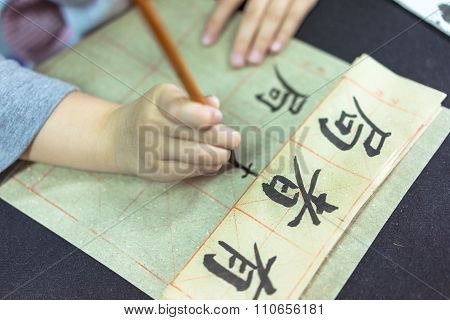 In October 18, 2015, a Chinese child with a brush in the classroom to learn to write Chinese calligr