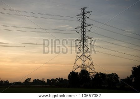 High Voltage Post Or High Voltage Tower In Rice Field, Sunrise