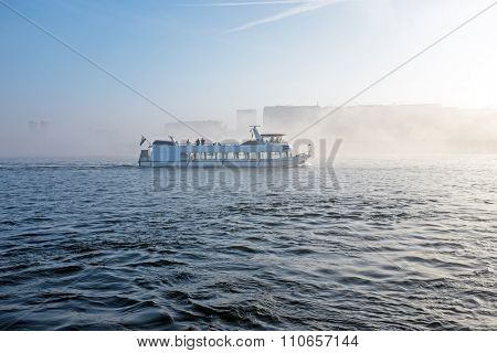 Cruiseboat in the fog in the harbour from Amsterdam in the Netherlands