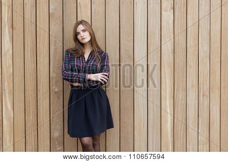Beautiful European female dressed in classy trendy clothes posing against wooden wall