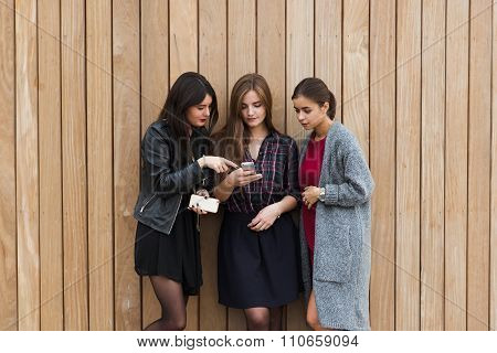 Attractive women watching something on cell telephone while standing outdoors