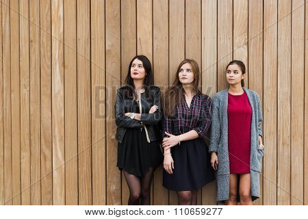 Cheerful ladies dreaming looking to the copy space area on wooden wall background
