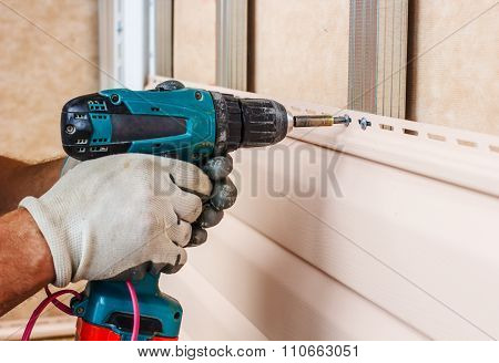 Man Screws In A Wall