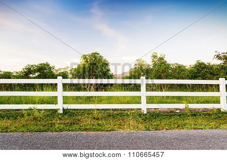 White Fence With Road And Blue Sky