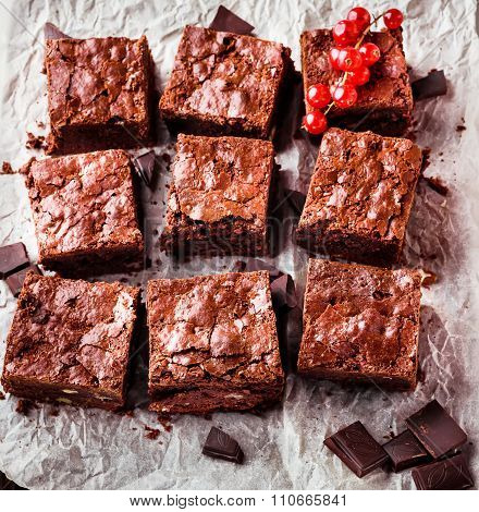 Brownie Pieces With Nuts Decorated With Berries  On The White Paper.