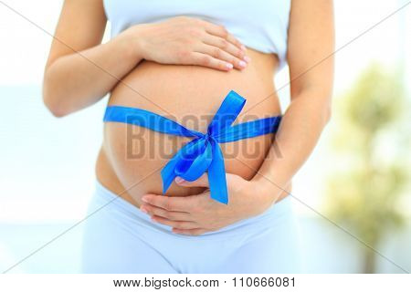 woman holding hands on her baby bump, tied with a blue bow