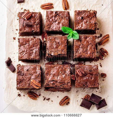 Brownie Pieces With Nuts On The White Paper Decorated With Mint Leaves.