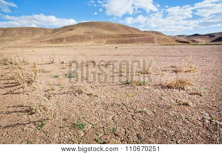 Mountains In The Distance Of The Desert Valley With Dry Soil Under The Scorching Sun Of The Middle E