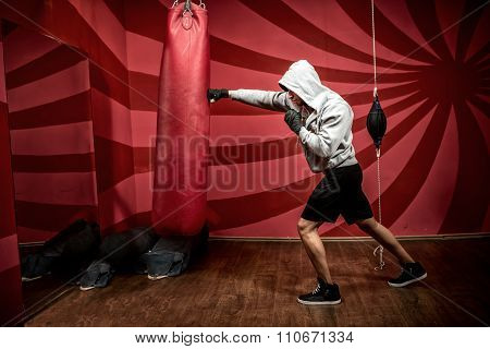 Athlete with hoody working out at boxing gym getting ready for fight