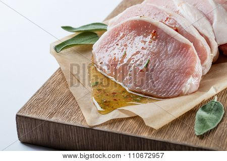 Raw meat. Pork escalope with sauce made of honey and herbs with green sage leaves on wooden board against white background. Top view