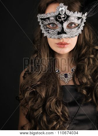 Beautiful woman  in a carnival mask on dark background.