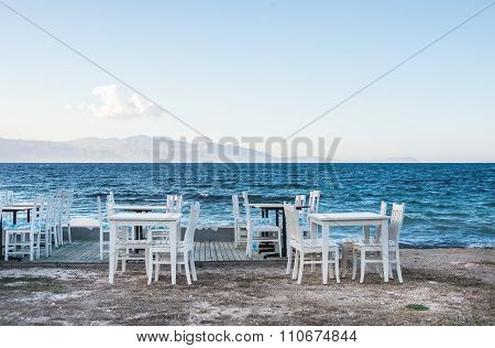 Chairs and tables in old cafe near the sea, Ciftlikkoy fishermen village, Aegean region, Turkey