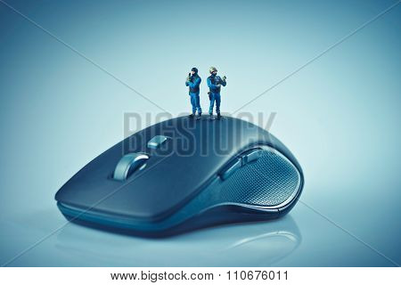 Miniature SWAT team on top of computer mouse. Computer security concept. Macro photo