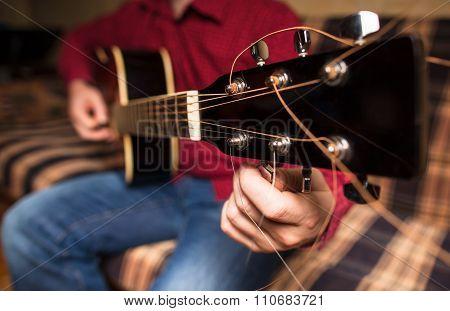 A Man Tuning A Guitar