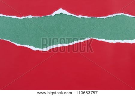 Hole ripped in red paper on green background. Copy space