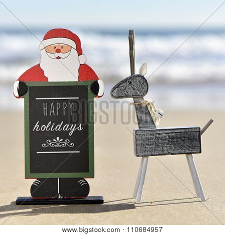a rustic wooden reindeer and a chalkboard in the shape of santa claus with the text happy holidays written in it on the sand of a beach