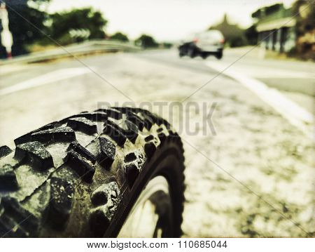 closeup of the wheel of a bycicle on the road
