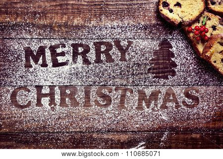 high-angle shot of a wooden table sprinkled with icing sugar where you can read the text merry christmas, and some pieces of fruitcake