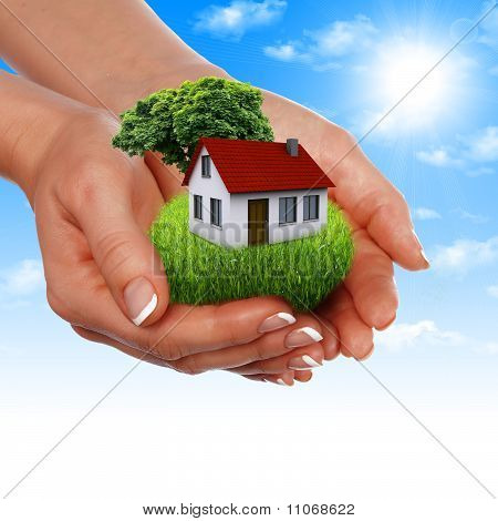 House in the hands against the blue sky