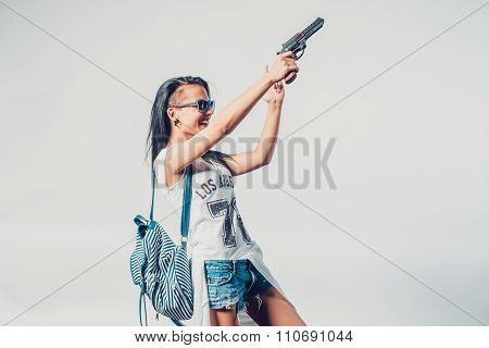 Fashion swag girl holding gun woman having fun  hooligan, rebel