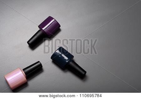 Three Nail Polish Bottles On A Gray Surface