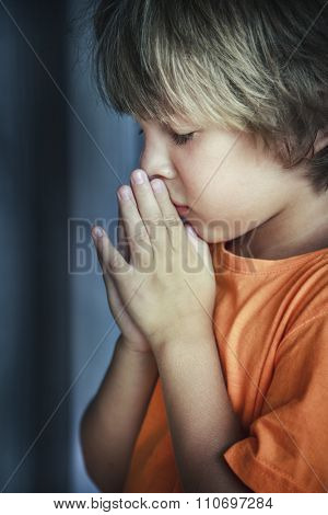 Little young beautiful boy spiritual peaceful praying and wishing