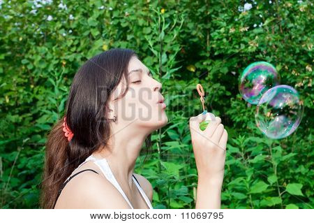 Portrait Of Funny Lovely Teenage Girl Inflating Colorful Soap Bubbles